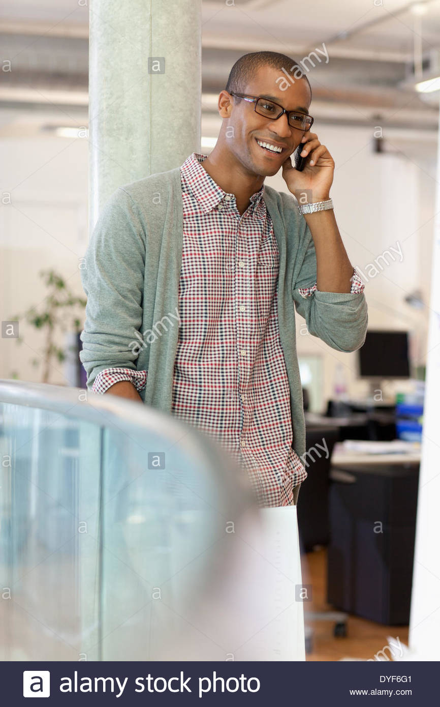 Businessman paperwork talking on cell phone in office - Stock Image