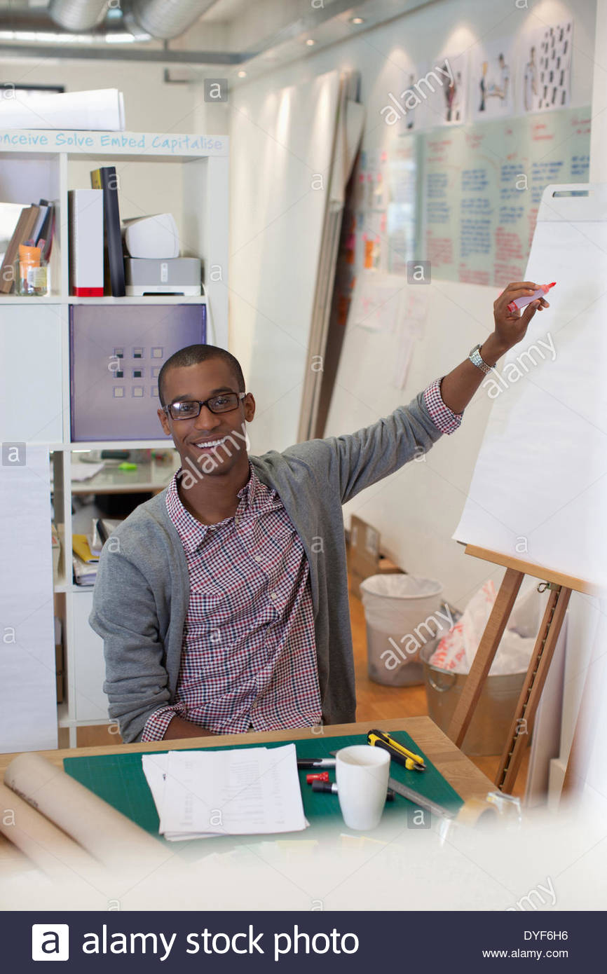 Businessman drawing diagram on flip chart in office - Stock Image