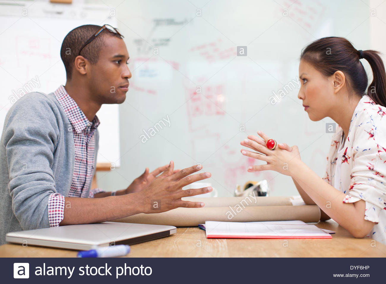 Businessman businesswoman sitting face to face in meeting - Stock Image