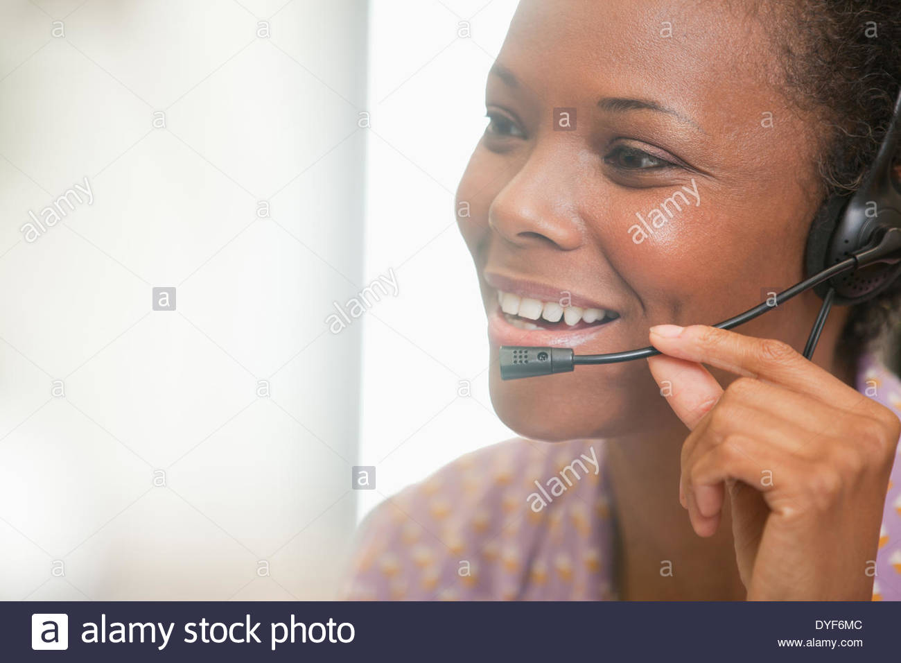 Close up of happy businesswoman using headset - Stock Image