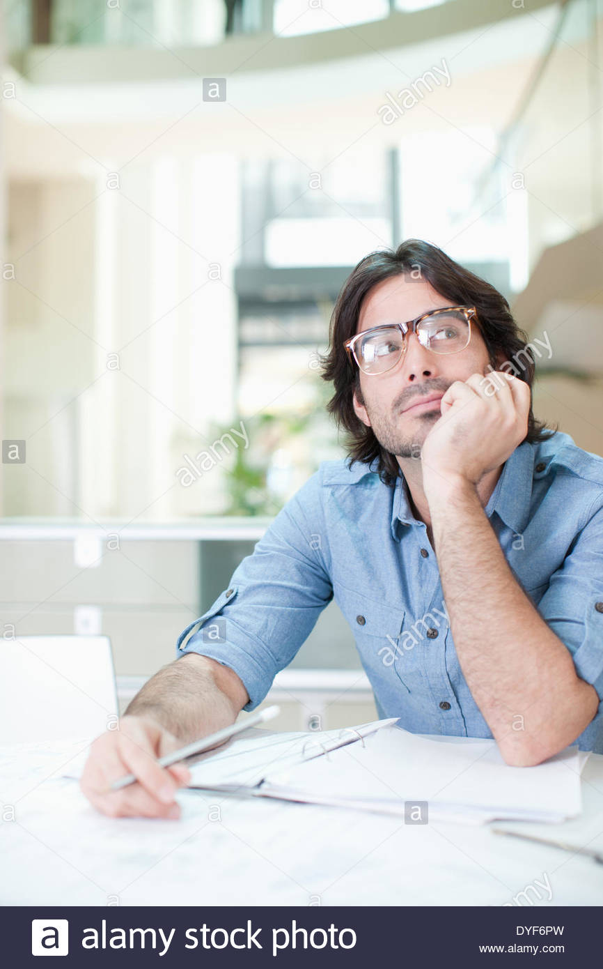 Businessman daydreaming at desk in office - Stock Image