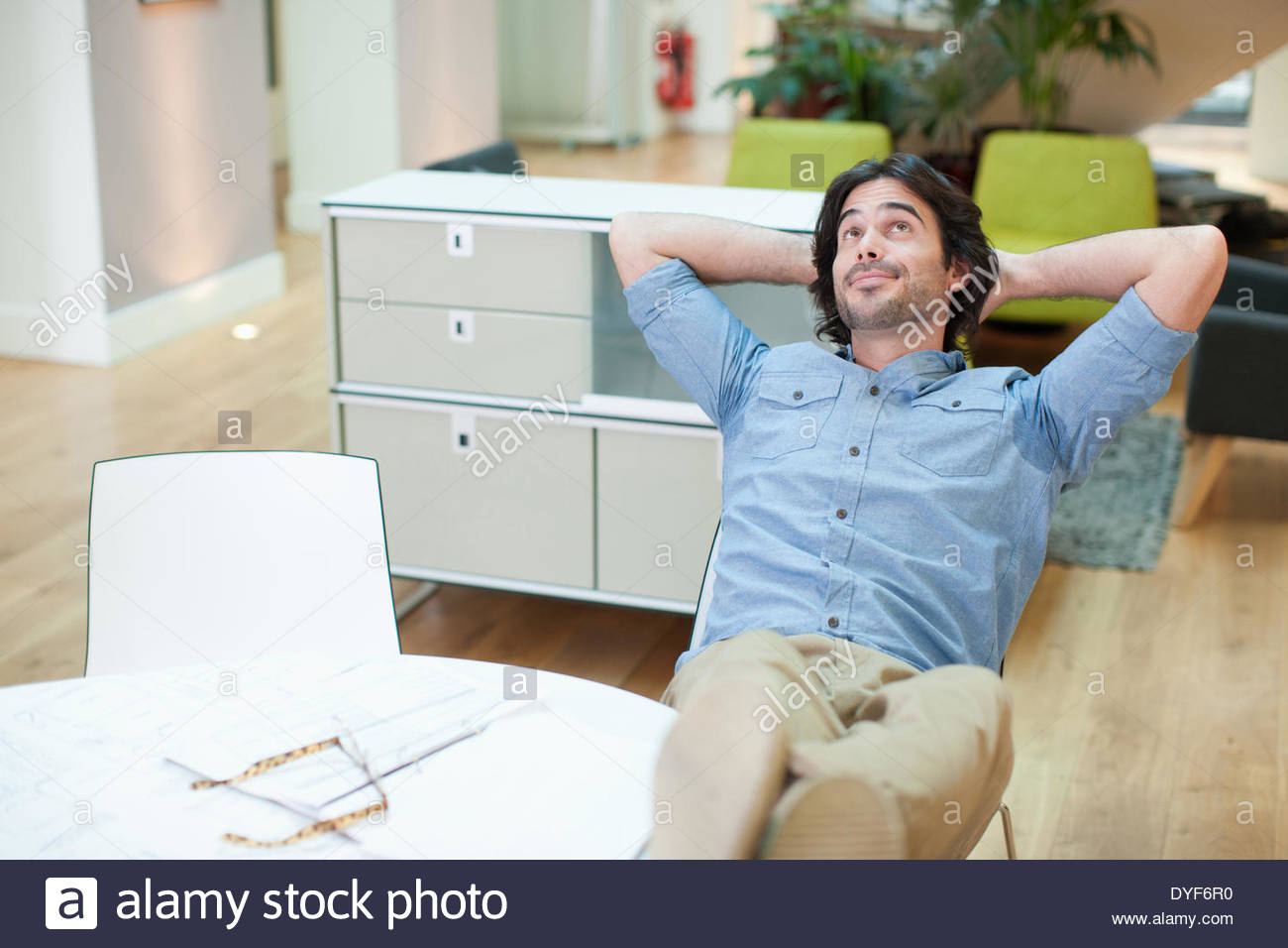 Successful man sitting hands behind head in office - Stock Image