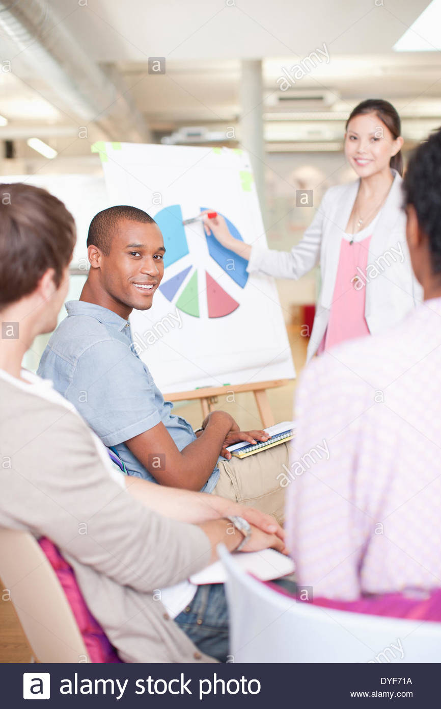 Business people in meeting looking at pie chart - Stock Image