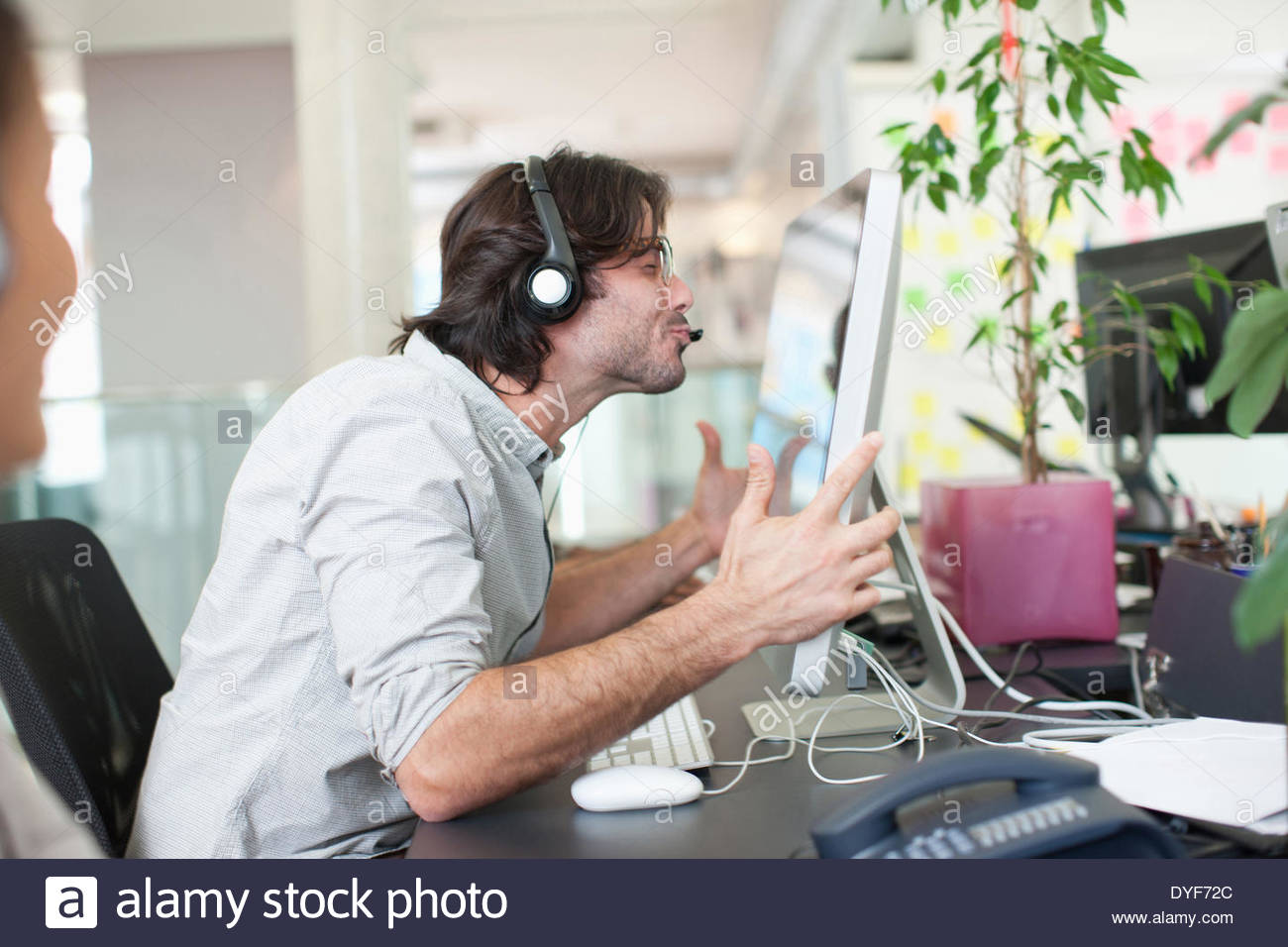 Business people headsets working computers in office - Stock Image