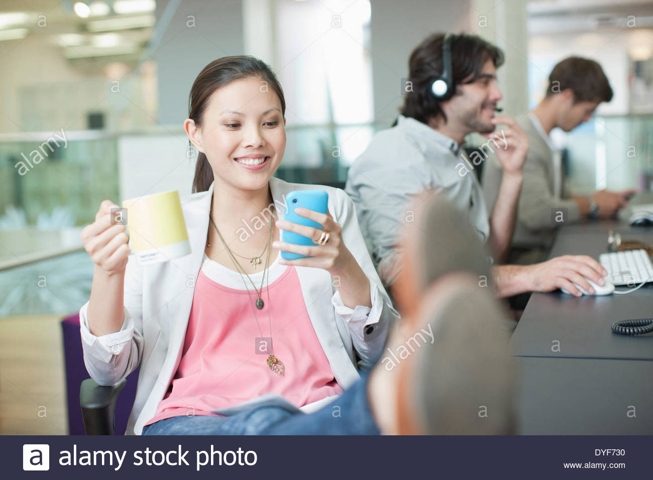 Businesswoman drinking coffee text messaging feet up in office - Stock Image