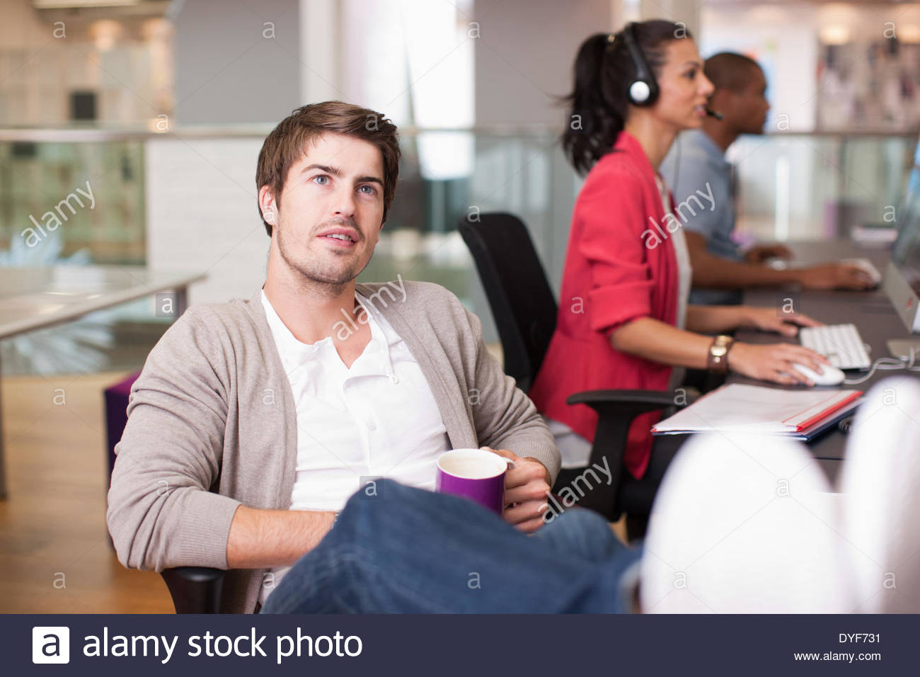 Businessman drinking coffee with feet up in office - Stock Image