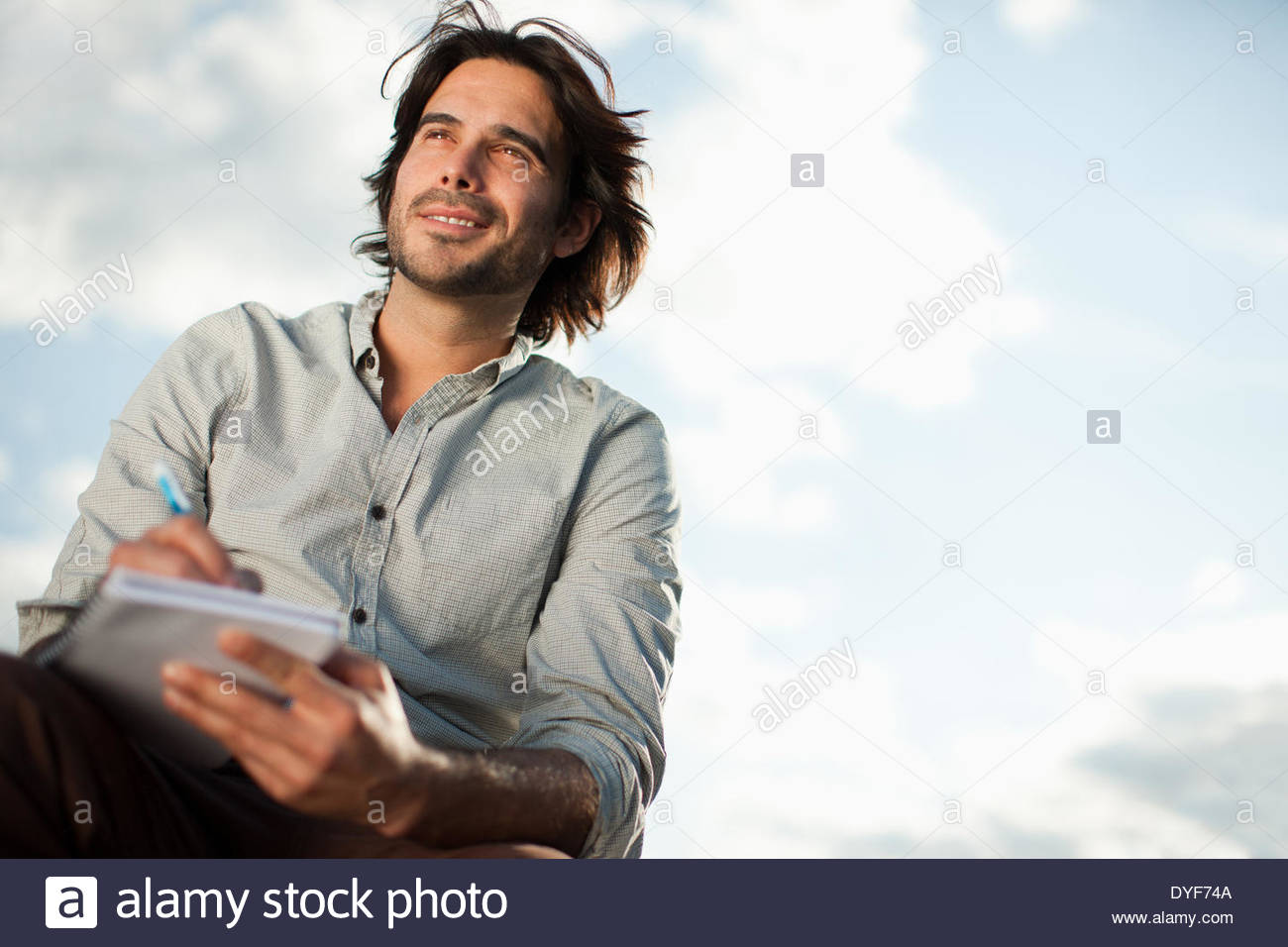 Pensive businessman writing in notebook outdoors - Stock Image