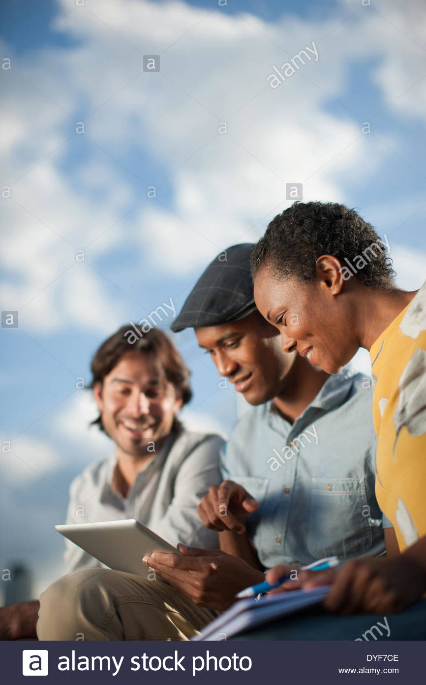 Business people sharing digital tablet in meeting - Stock Image