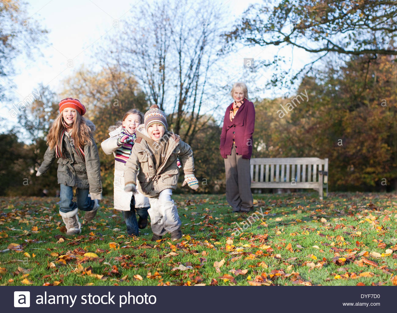 Grandmother playing with grandchildren outdoors - Stock Image