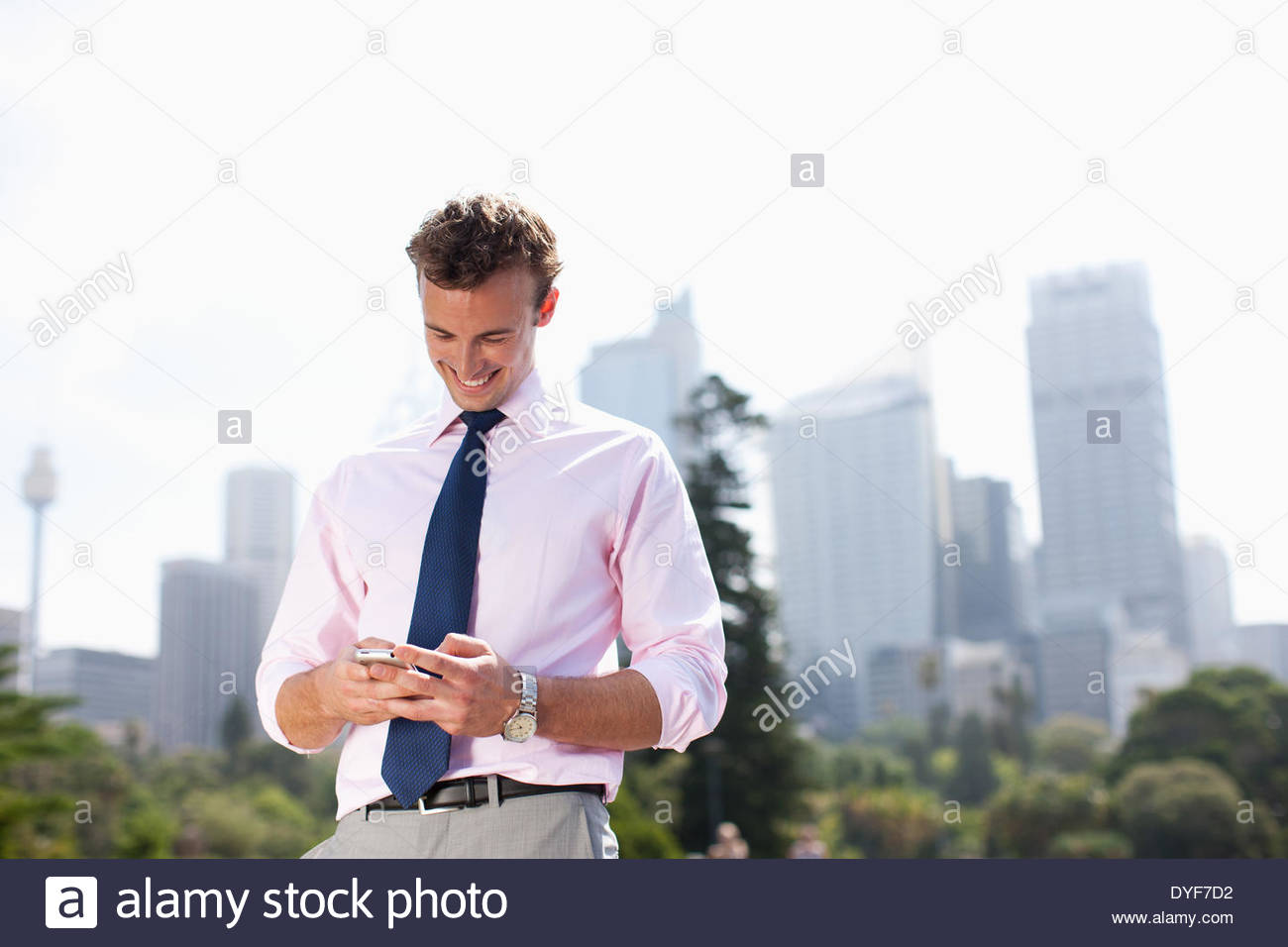 Businessman text messaging on cell phone outdoors - Stock Image