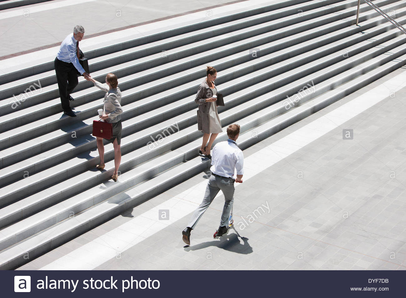 Business people shaking hands on steps outdoors - Stock Image