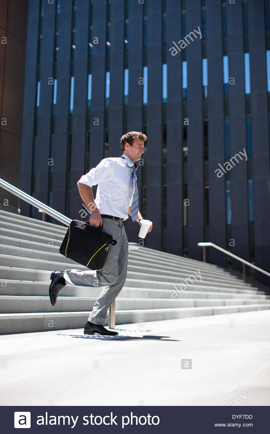 Businessman rushing down steps outdoors - Stock Image