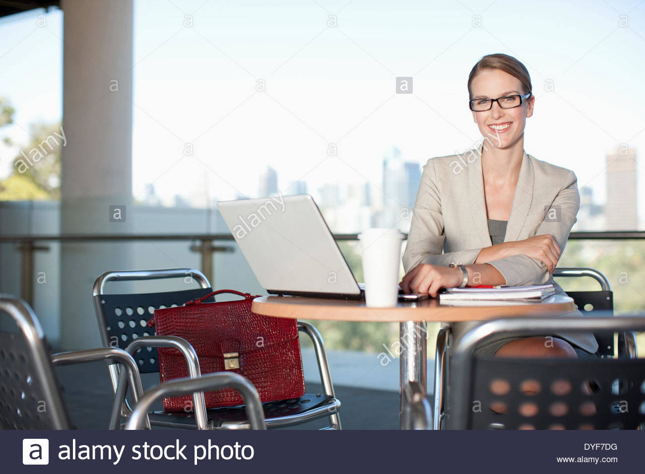 Smiling businesswoman  in cafe with laptop - Stock Image