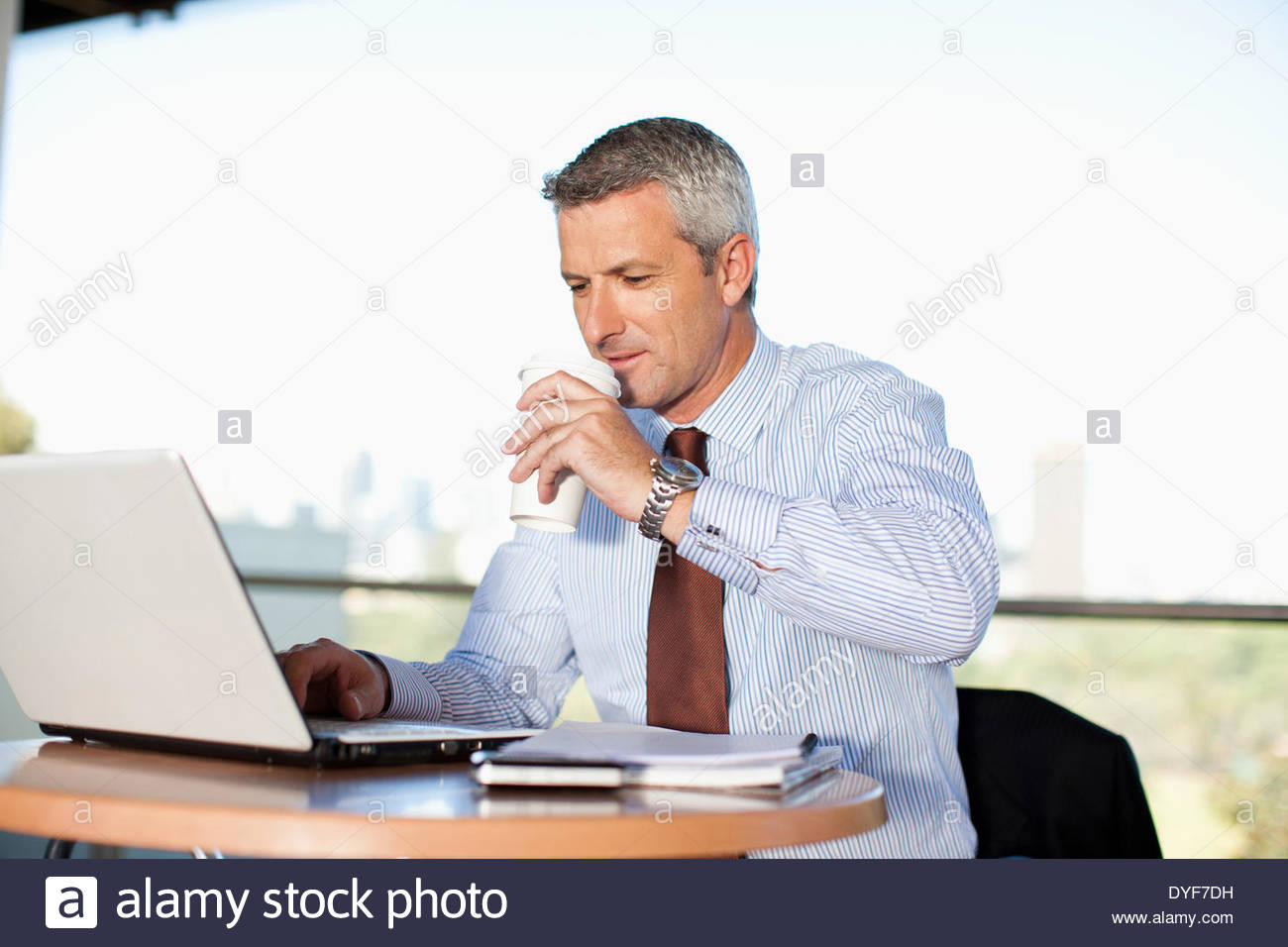 Businessman using lapto pand drinking coffee in cafe - Stock Image