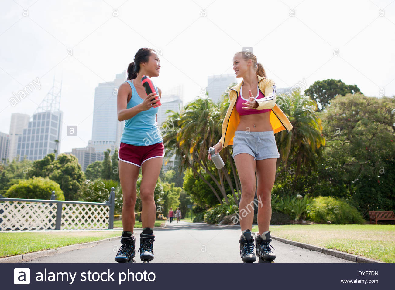 Friends inline skating in park - Stock Image