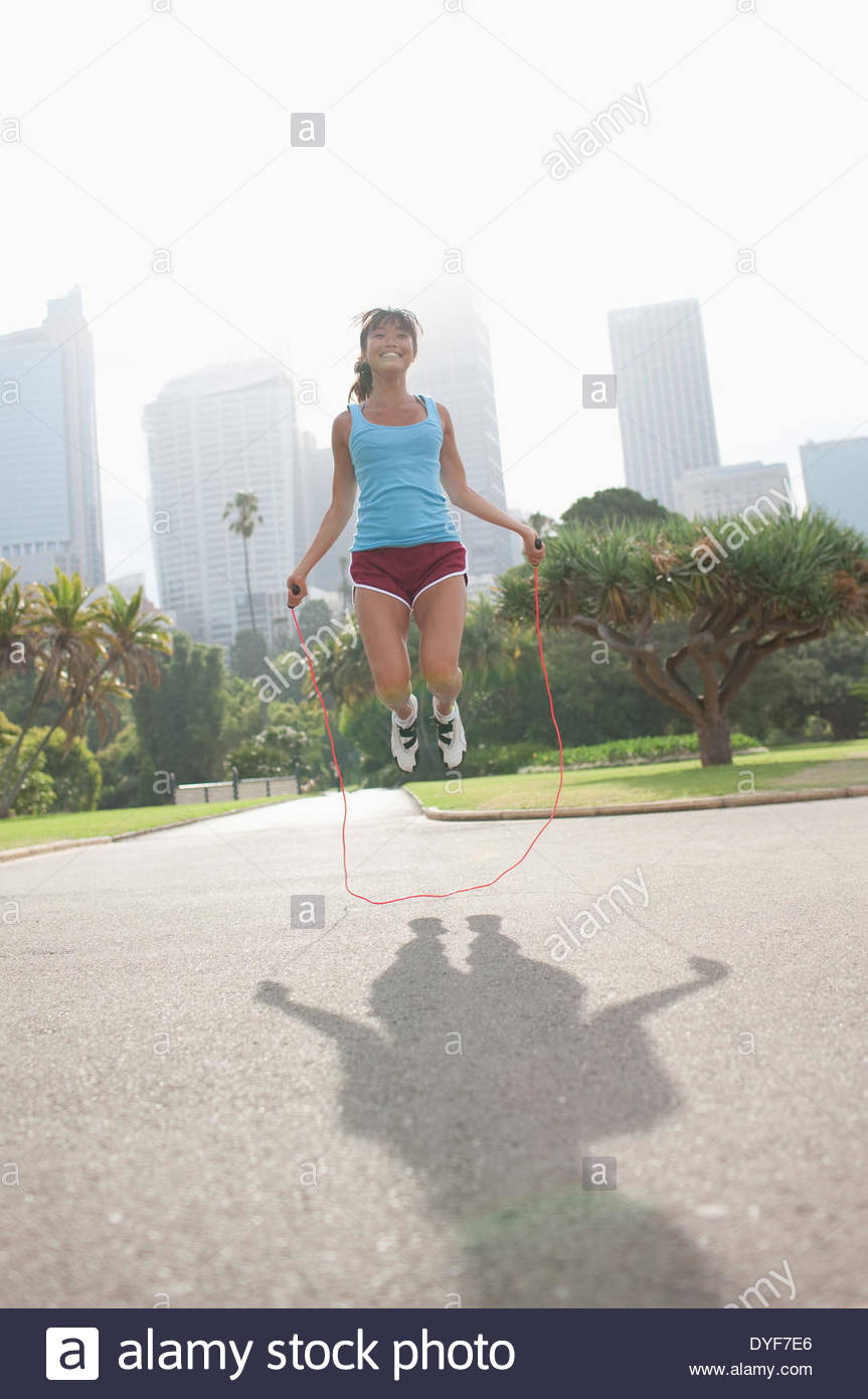 Woman skipping rope in park - Stock Image