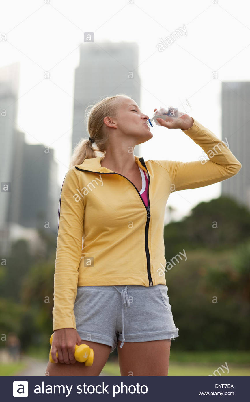 Woman drinking water after exercise - Stock Image