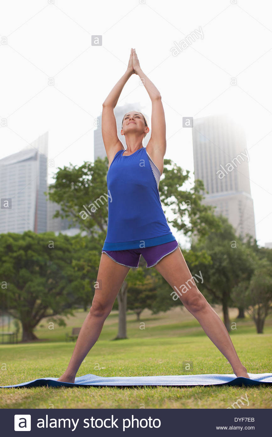 Woman practicing yoga in park - Stock Image
