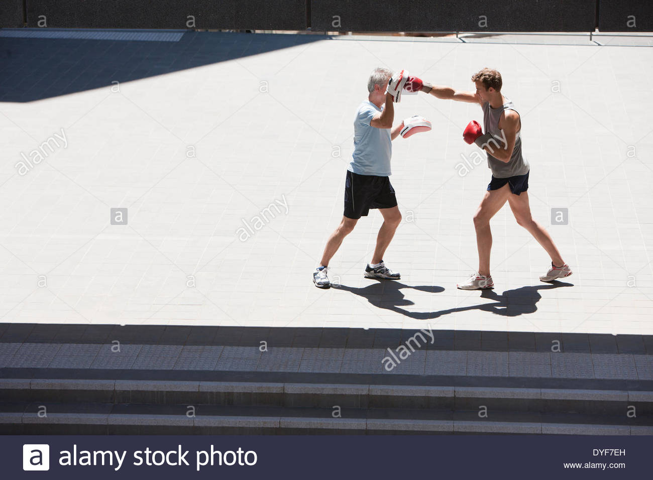 Boxer training with coach outdoors - Stock Image