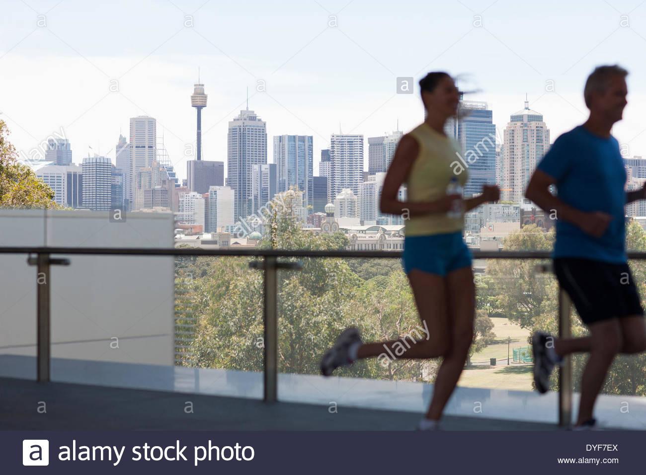 Couple running in urban setting - Stock Image