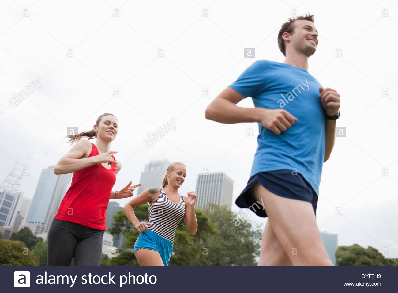 Friends running in urban park - Stock Image