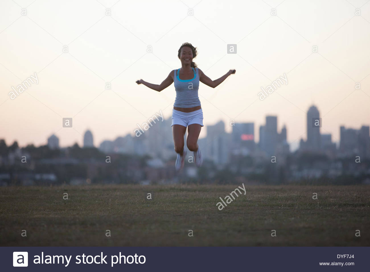 Woman practicing yoga in urban park - Stock Image