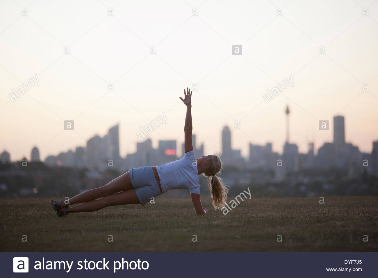 Woman practicing yoga in urban park Stock Photo