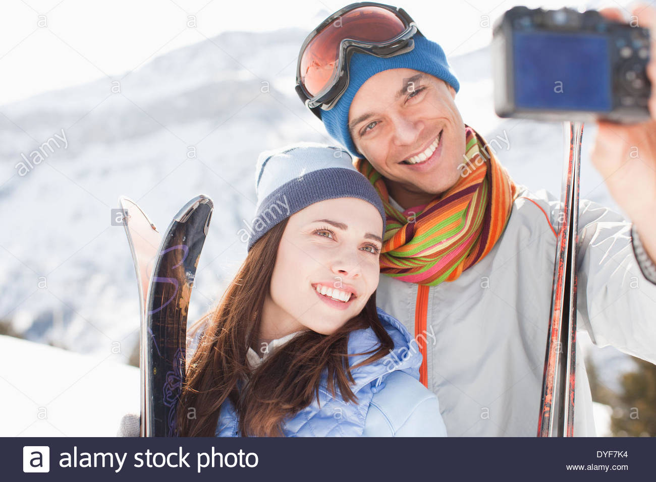 Couple with skis taking self-portrait - Stock Image