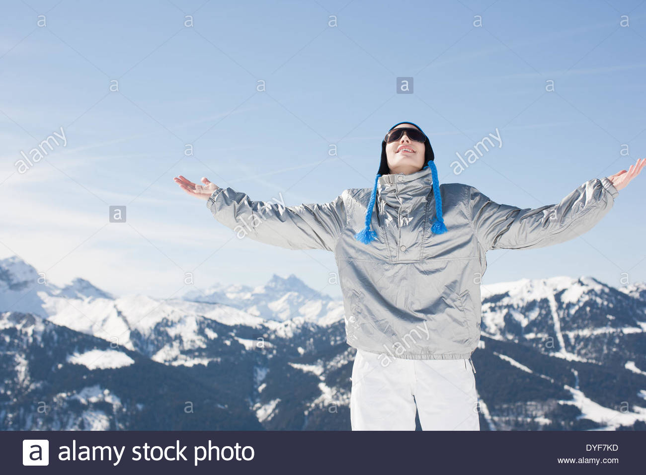 Woman with arms outstretched in snow - Stock Image