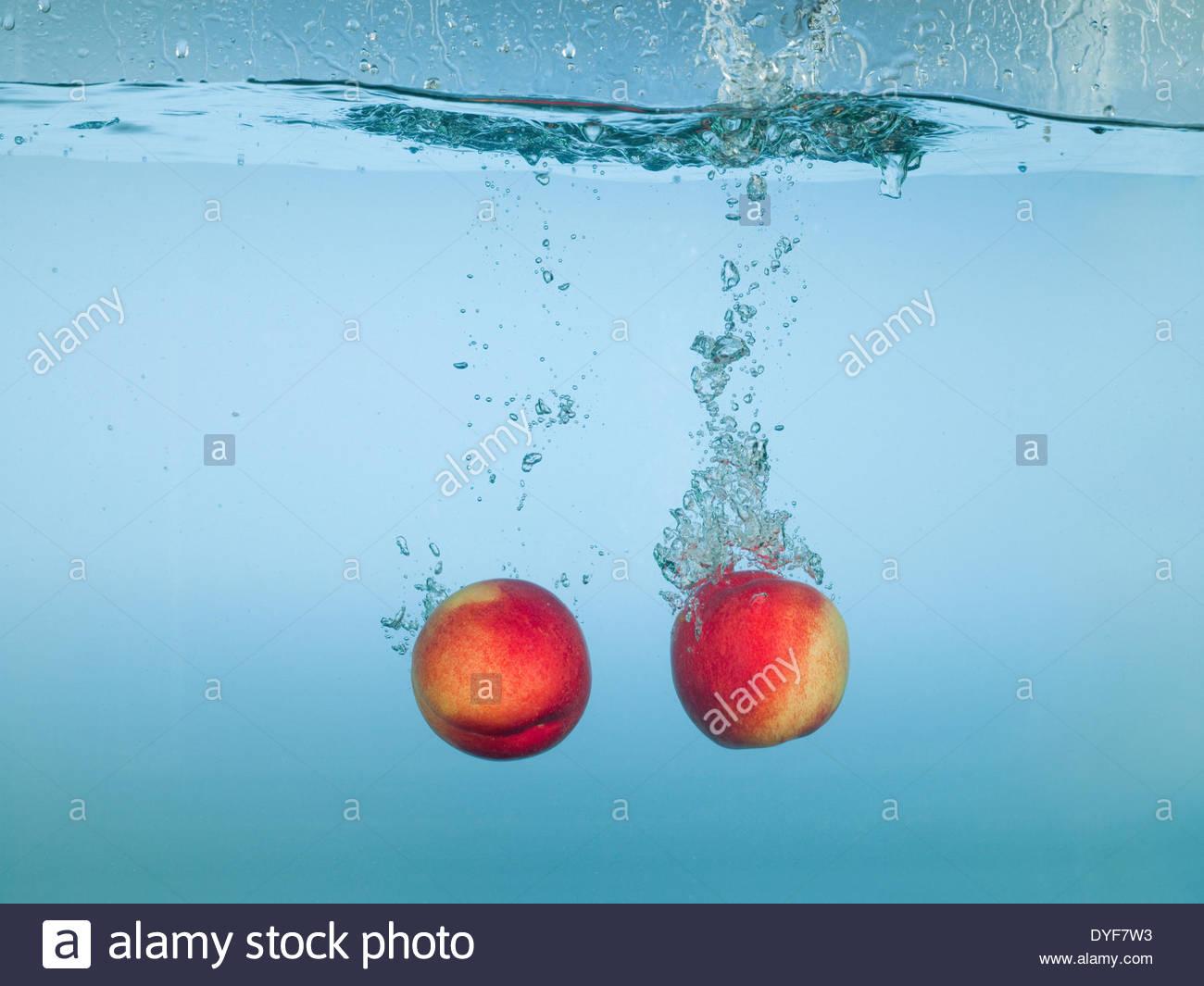Apples splashing in water - Stock Image