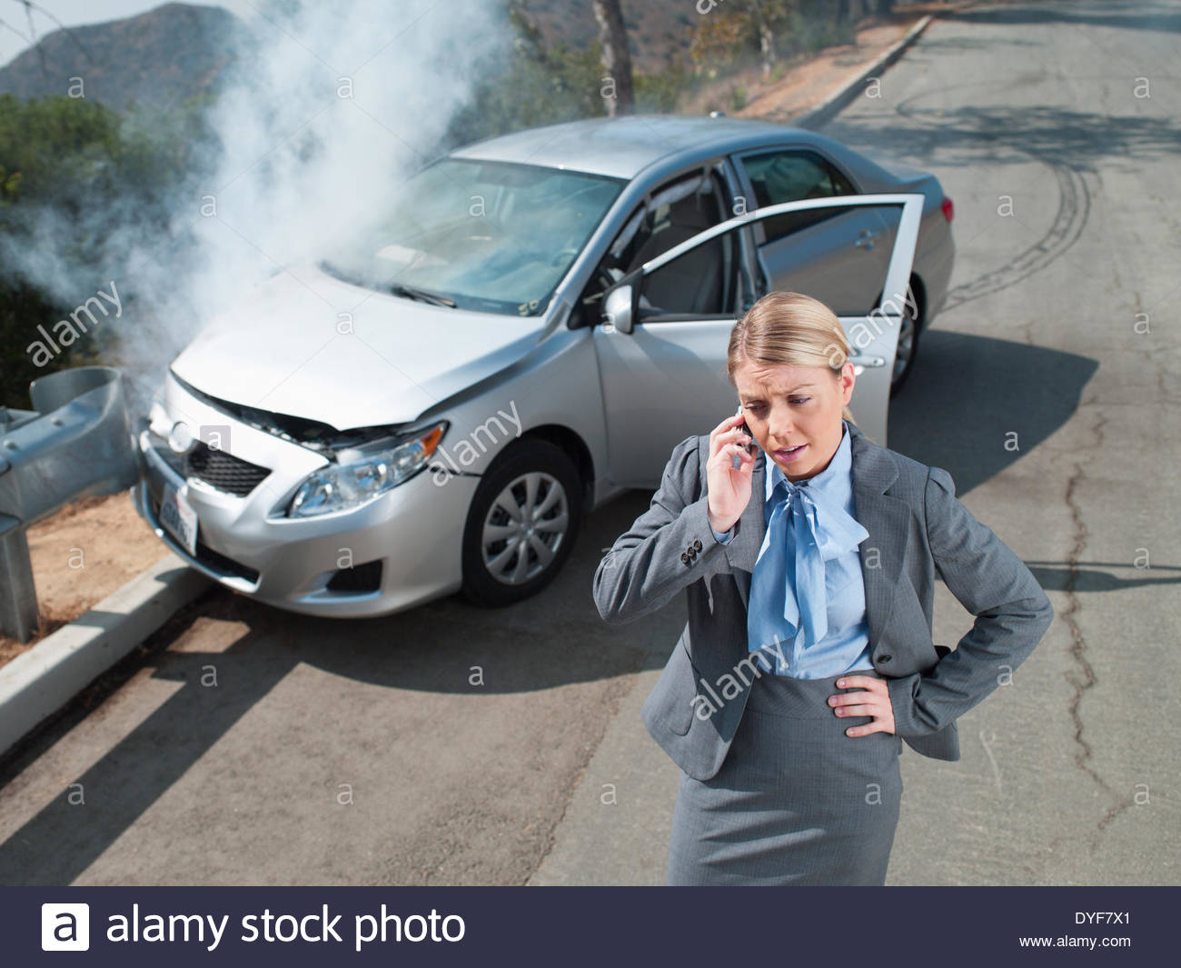 Businesswoman using cell phone near car wrecked on guardrail - Stock Image
