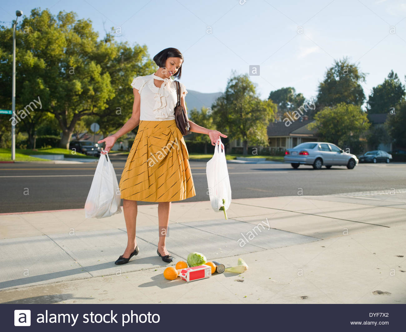Frustrated woman dropping groceries on sidewalk - Stock Image
