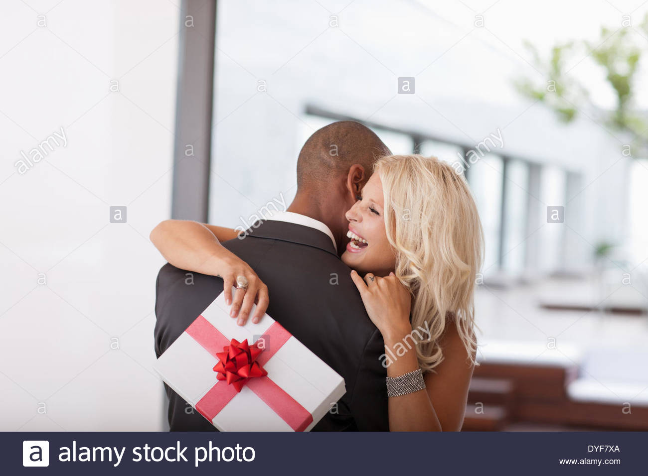 Woman with gift hugging man - Stock Image