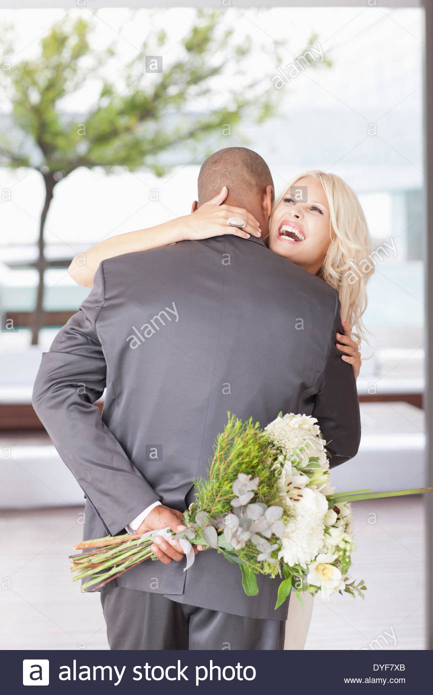 Woman with flowers hugging man - Stock Image