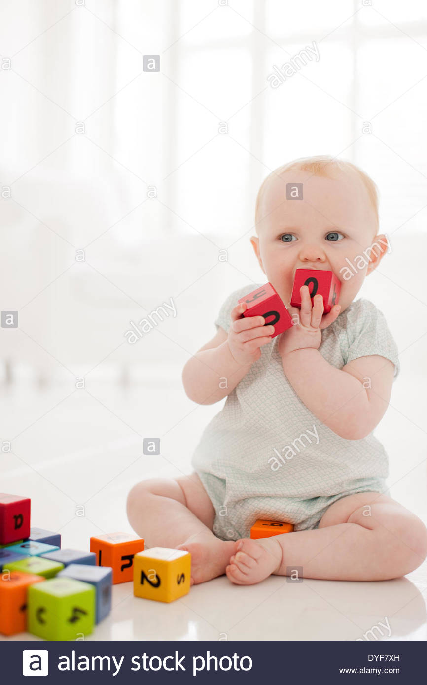 Baby biting wood block - Stock Image