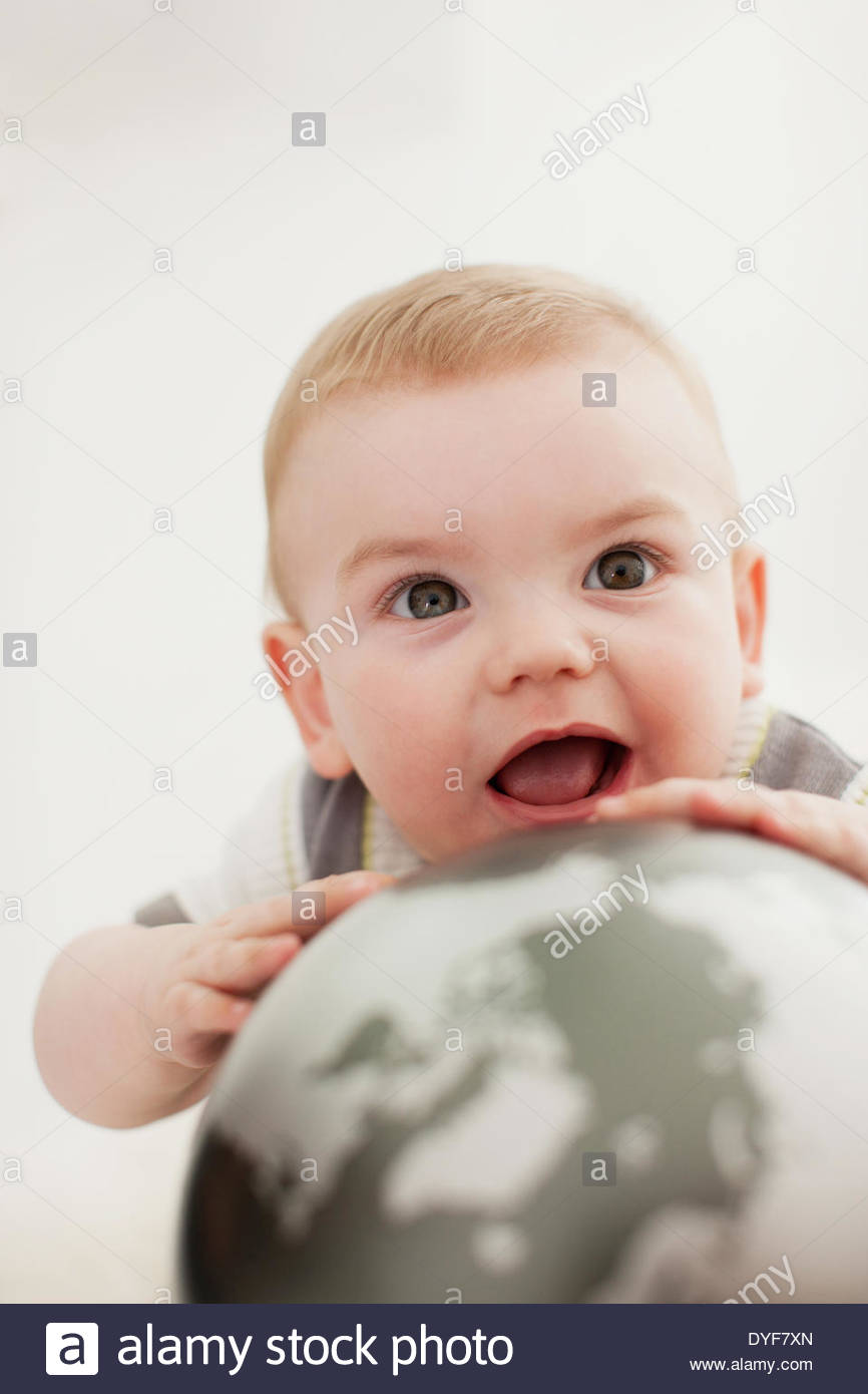 Close up of baby holding globe - Stock Image