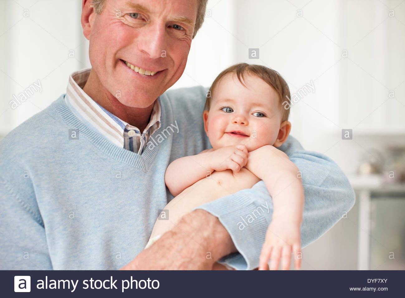 Smiling grandfather holding baby - Stock Image