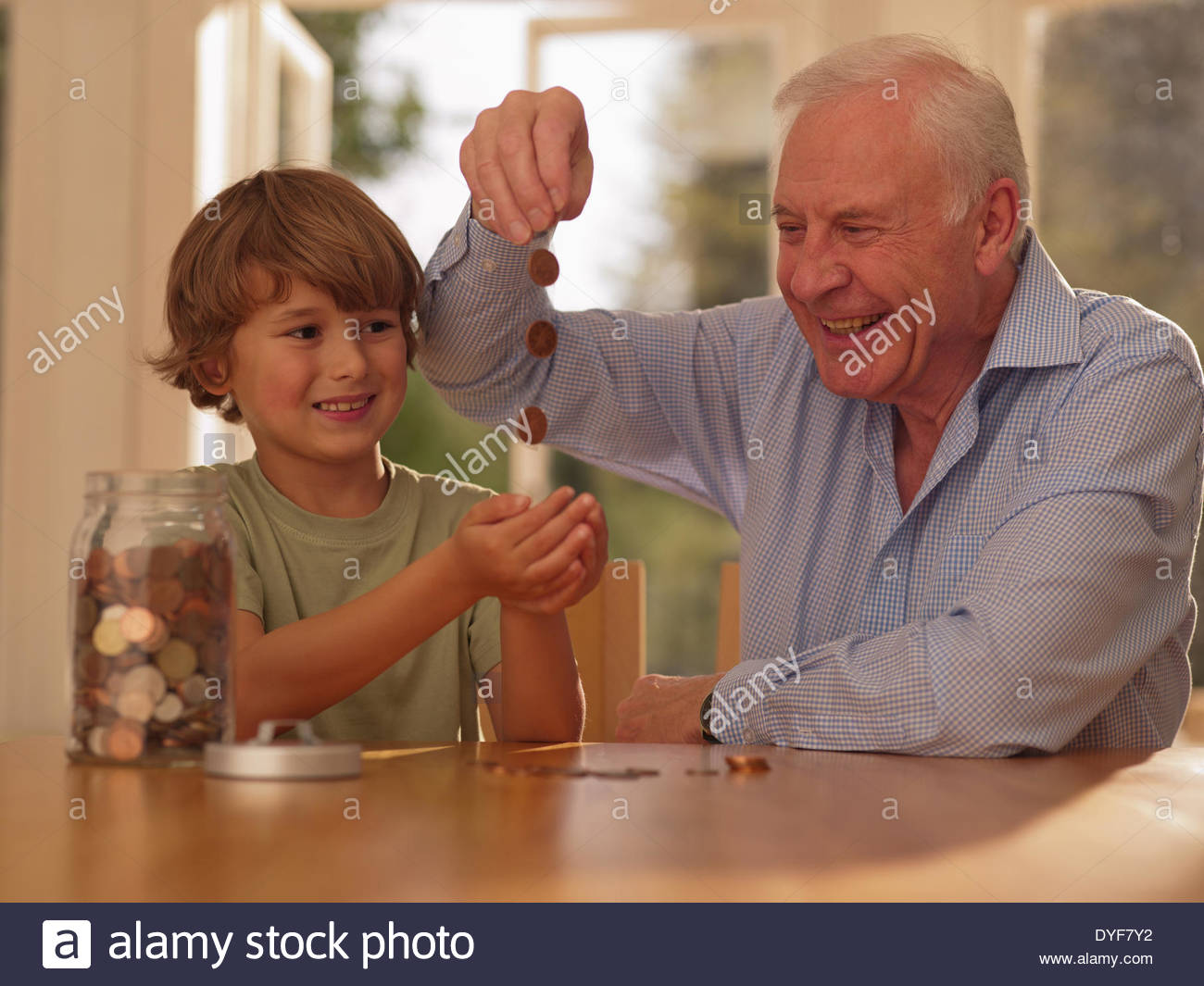 Grandfather and grandson with jar of coins - Stock Image