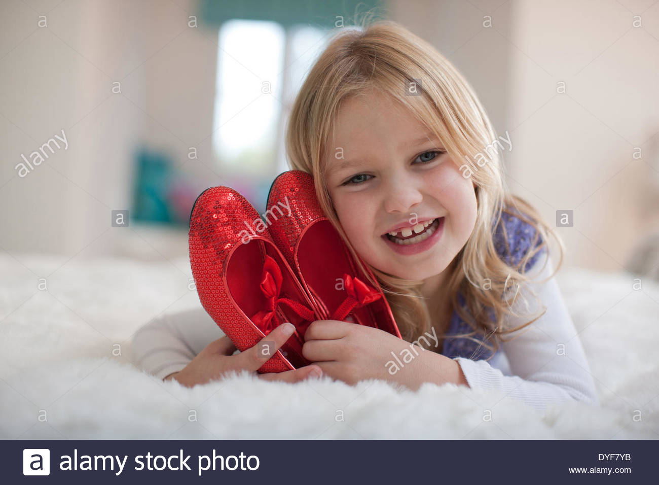 Smiling girl holding red shoes - Stock Image