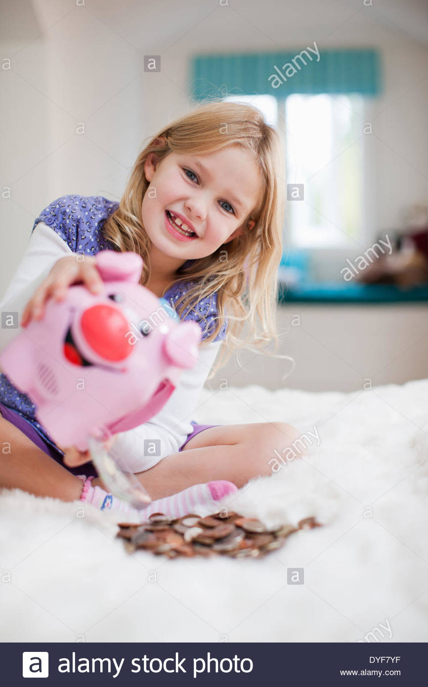 Grinning girl with piggy bank - Stock Image