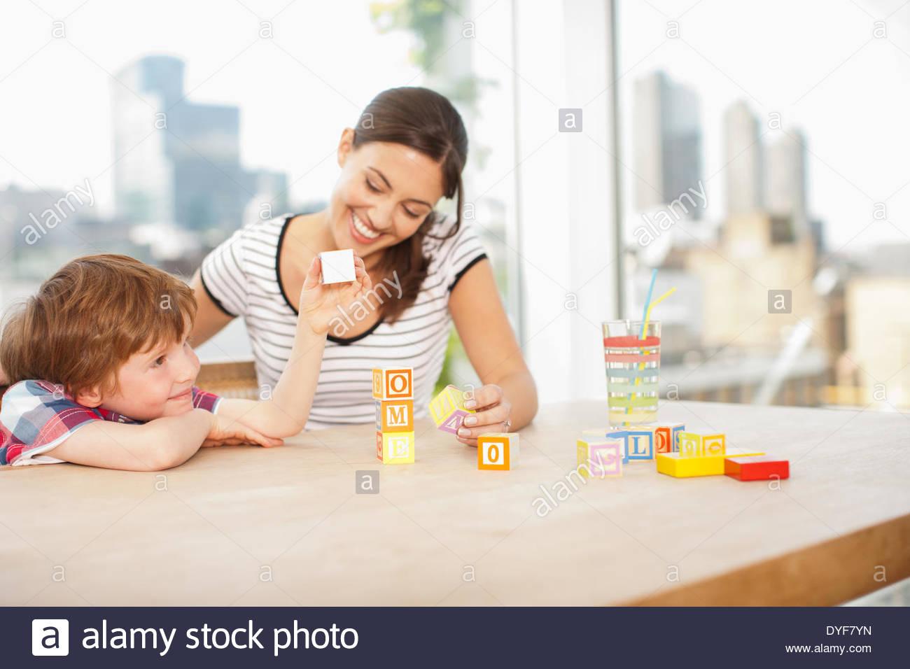 Mother watching son stacking alphabet blocks spelling Â'homeÂ' - Stock Image