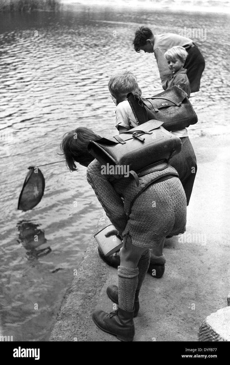Children are trying to 'fish' on their way home from school. Picture taken in 1948 in Berlin. - Stock Image