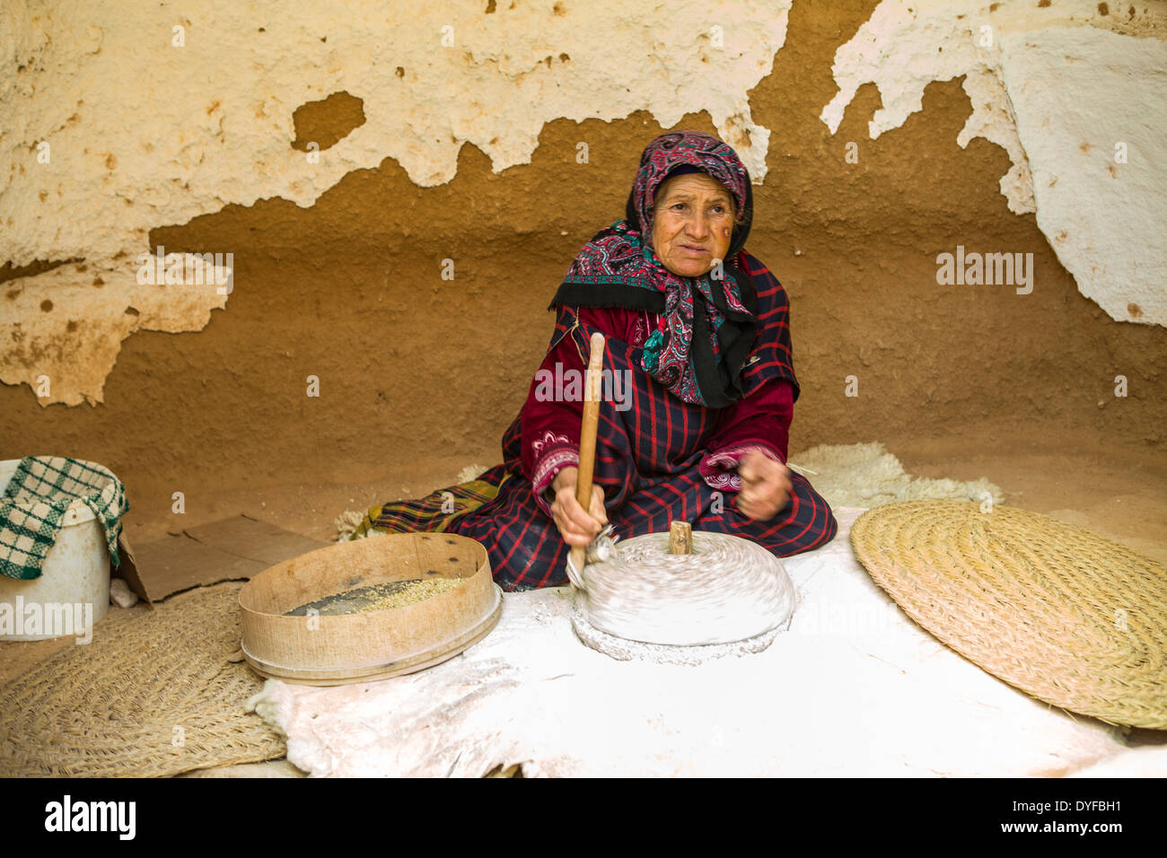 A Berber female grinding to prepare flour for bread. - Stock Image