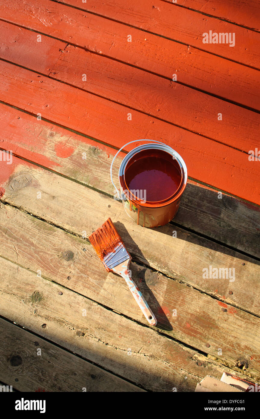 Re-staining old wooden deck DIY project painted into corner. - Stock Image