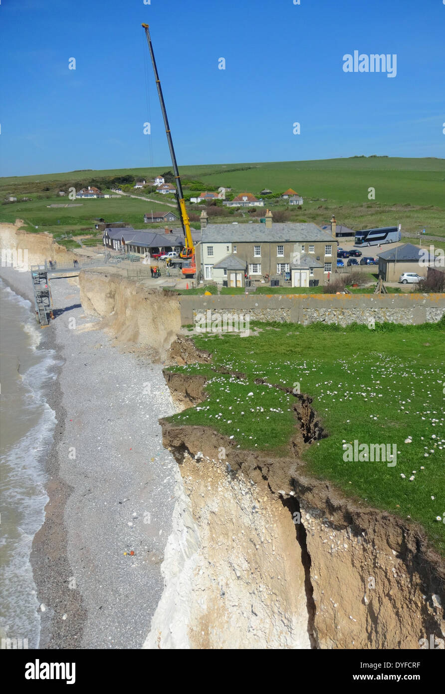Birling Gap, East Sussex, UK..16th April 2014..Final day of demolition at Coastguard cottages. Crane and basket brought in to safely remove overhanging cliff face debris.All equipment will be removed from site tomorrow. Rock falls still continue along the fragile chalk cliffs.This section of cliff still hangs on the crack and chasm below very clear in this picture. Photographer used specialist equipment and did not take risks. Credit:  David Burr/Alamy Live News - Stock Image