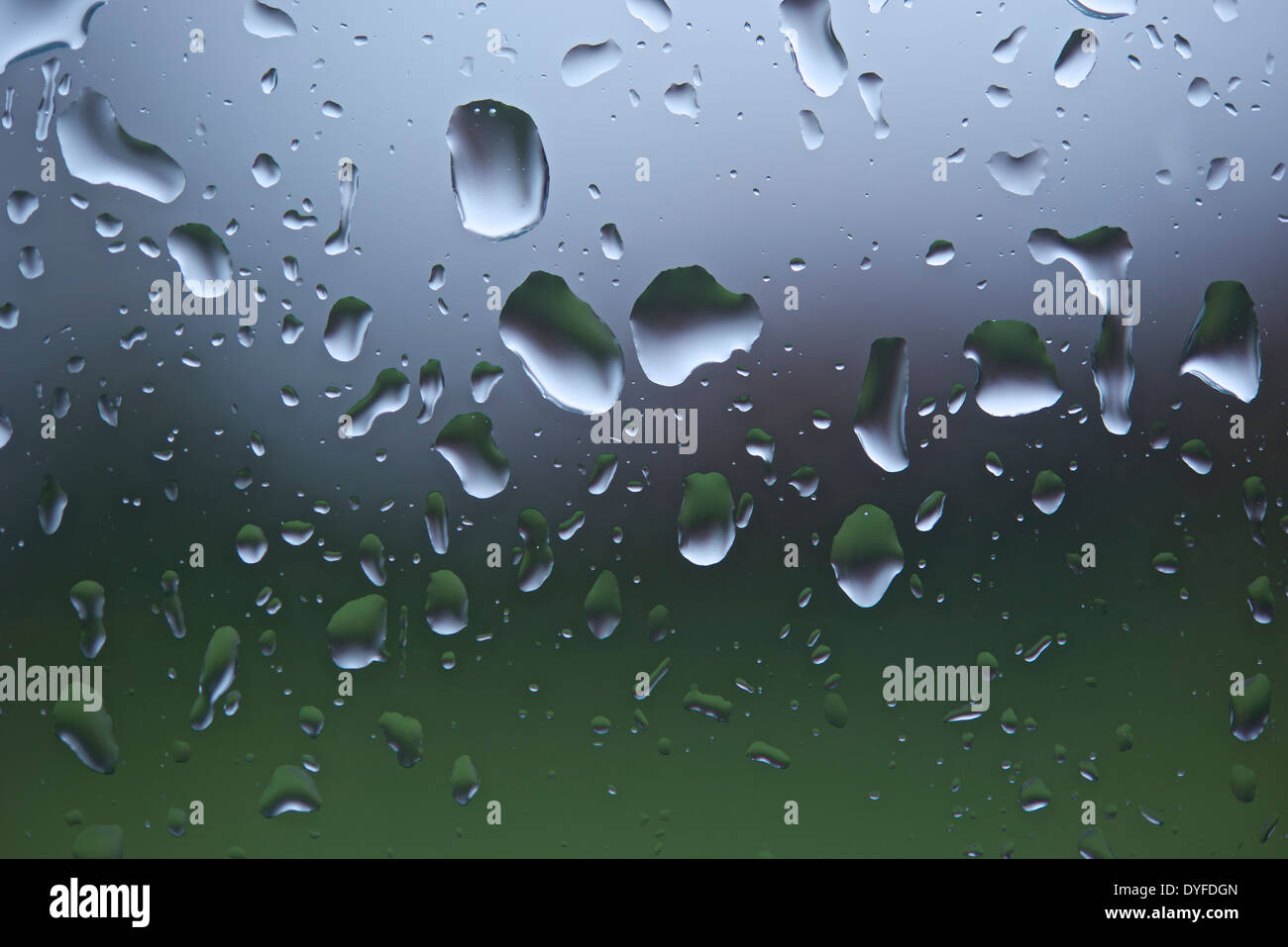 Close-up of raindrops on a window pane after heavy rain with background thrown out of focus. - Stock Image