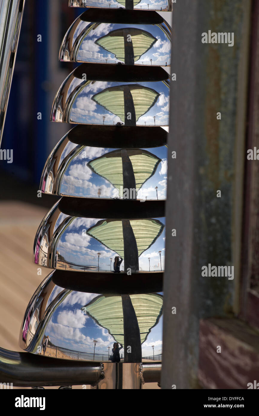 Photographer at Boscombe pier reflected in Bell Lyre percussion instruments on Boscombe pier in April - Stock Image