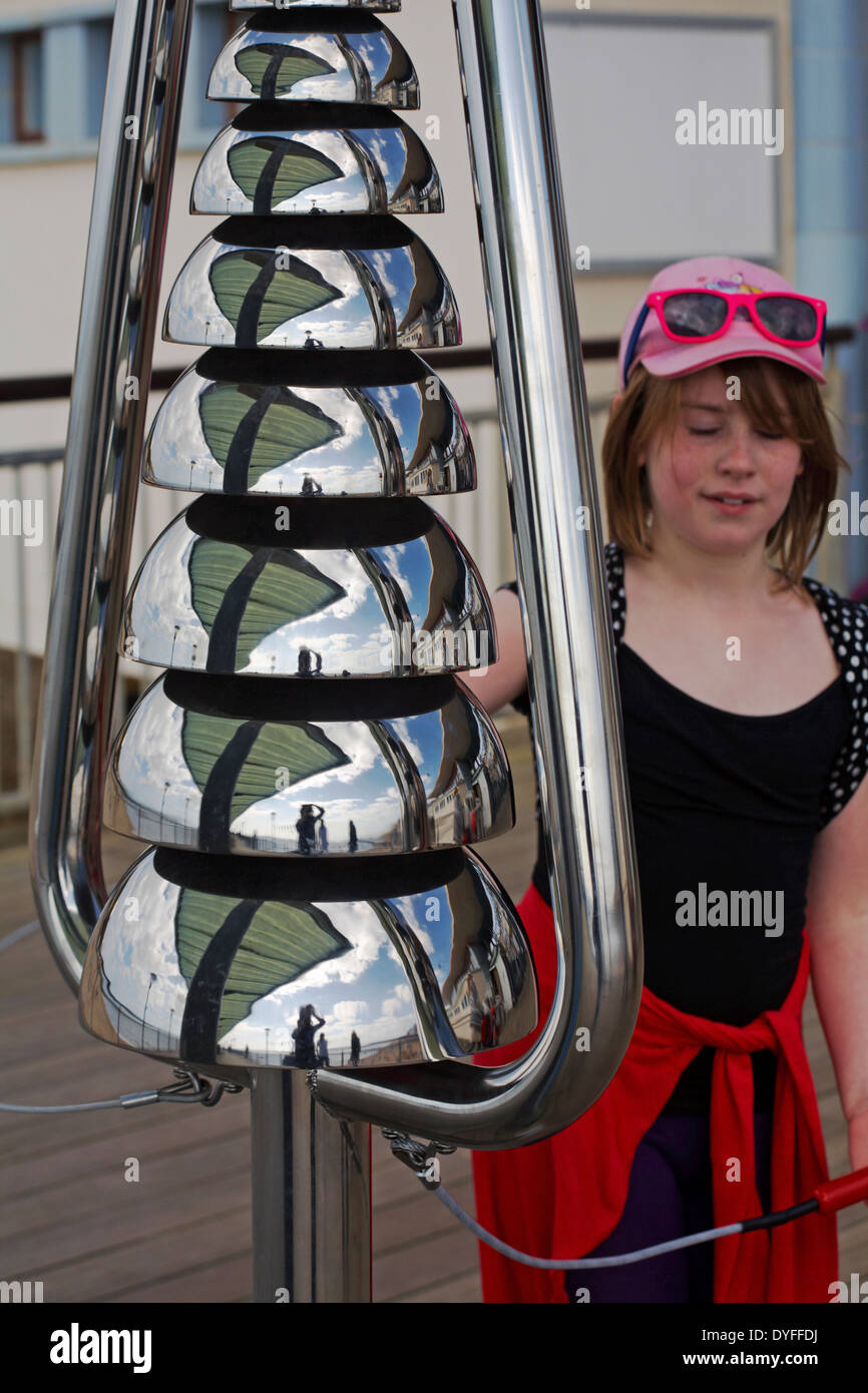 Photographer at Boscombe pier reflected in Bell Lyre percussion instruments with young girl playing on Boscombe pier in April - Stock Image