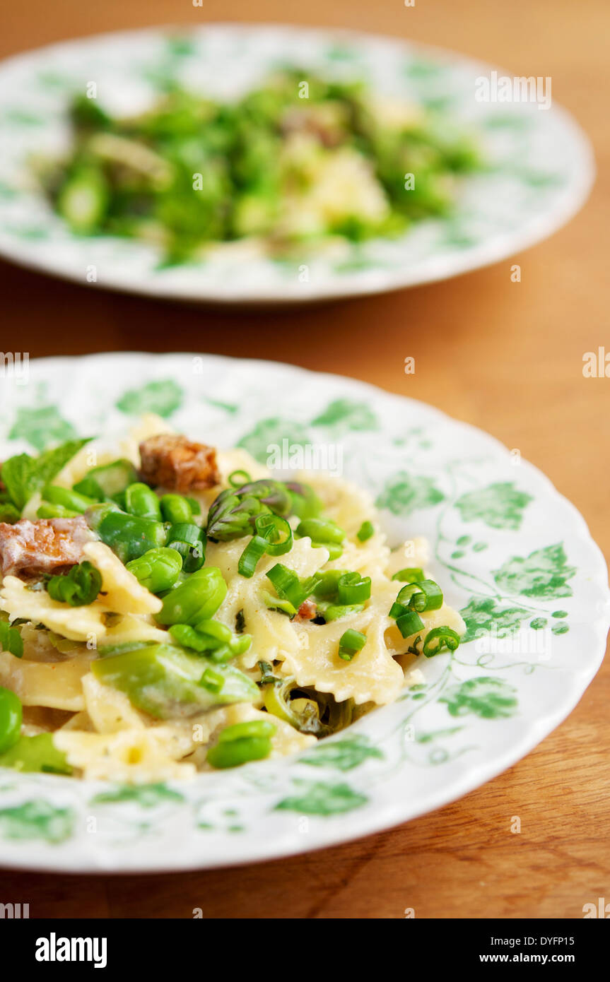 This spring meal with fresh fava beans, green asparagus and bow tie pasta was delicious. - Stock Image