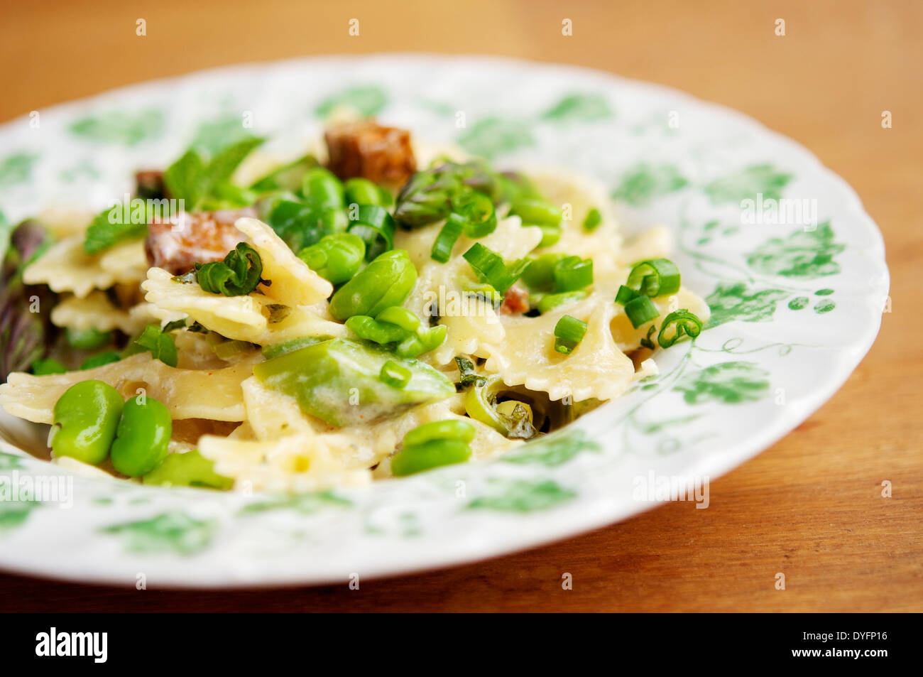 Spring meal with fresh fava beans, green asparagus, bow tie pasta and spicy tofu pieces. - Stock Image